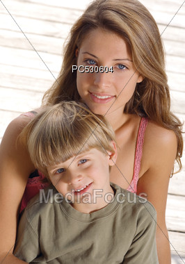 Young Woman & Boy Sitting On The Dock Stock Photo