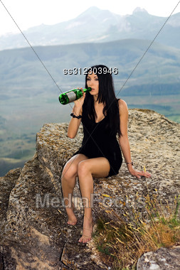 Young Woman With A Champagne Bottle Sits On A Rock Stock Photo