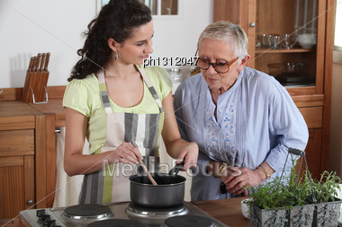 Young Woman Cooking For An Elderly Lady Stock Photo
