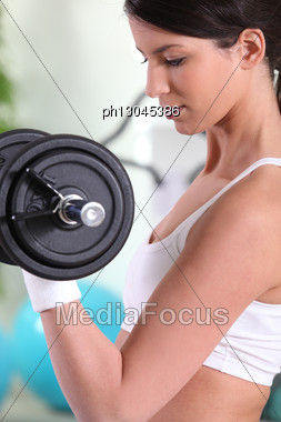 Young Woman Doing Bicep Curls In A Gym Stock Photo
