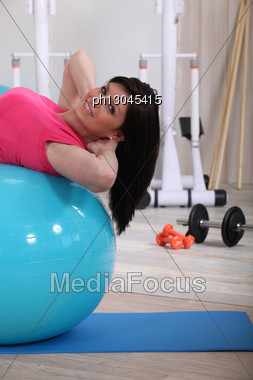 Young Woman Doing Stability Ball Abs Exercises In The Gym Stock Photo