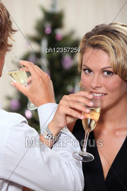 Young Woman Drinking Champagne With Her Boyfriend At Christmas Stock Photo