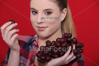 Young Woman Eating Grapes On Red Background Stock Photo