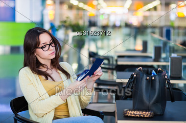 Young Woman Examining Her Tickets In The Airport Waiting Room Stock Photo