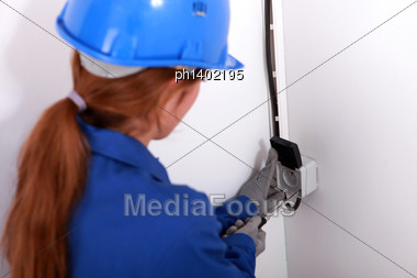 Young Woman Fitting An Electrical Socket Stock Photo