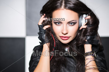 Young Woman With Headphones Posing In The Studio Stock Photo