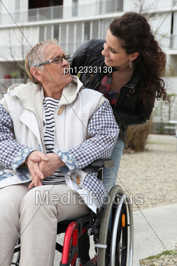 Young Woman Helping A Senior In A Wheelchair Stock Photo