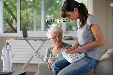 Young Woman Helping Senior Lady With The Housework Stock Photo