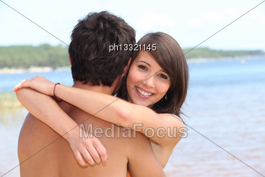 Young Woman Hugging Boyfriend At Beach Stock Photo