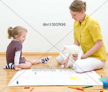 Young Woman And Little Girl Drawing Together Sitting On The Floor Stock Photo