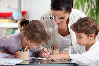 Young Woman And Little Girls Making Coloring Stock Photo