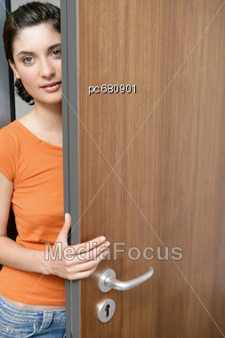 Royalty-Free Stock Photo: Young Woman Looks From Behind Door