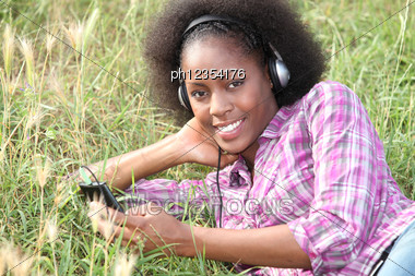 Young Woman Lying On The Grass And Listening Music Stock Photo
