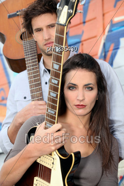 Young Woman And Man Playing In A Music Band Stock Photo