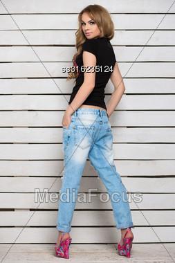 Young Woman Posing In Blue Jeans And Black T-shirt Near White Wooden Wall Stock Photo