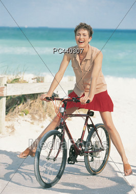 Young Woman Riding A Bicycle On The Beach Stock Photo