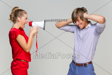 Young Woman Screaming At Her Boyfriend With Mehaphone Over Grey Background Stock Photo