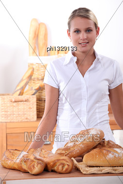 Young Woman Selling Bread Stock Photo