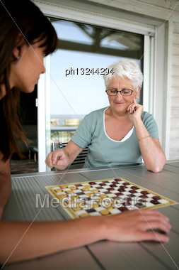 Young Woman And Senior Woman Playing Checkers Stock Photo