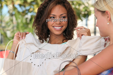 Young Woman Showing Off A New Top To A Girlfriend Stock Photo