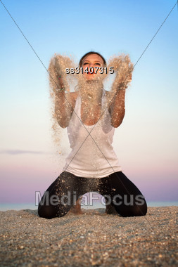 Young Woman Sitting On The Beach And Throwing Sand Stock Photo