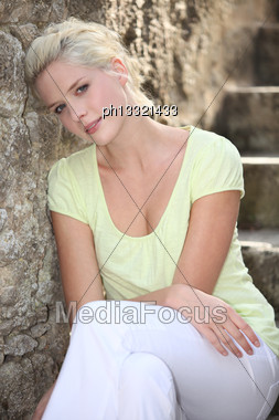 Young Woman Sitting On Stone Stairs Stock Photo