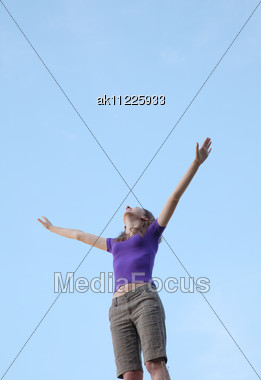 Young Woman Sitting With Raised Hand Against Blue Sky Stock Photo