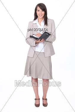 Young Woman In A Skirt Suit Writing In A Personal Organizer Stock Photo