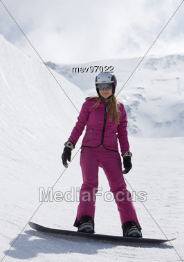 Young Woman Standing on Snowboard Stock Photo