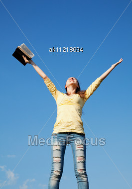 Young Woman Staying With Raised Hands Against Blue Sky Stock Photo
