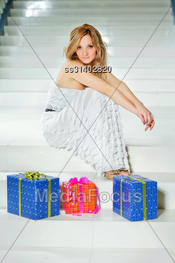Young Woman With Three Gifts Sitting On The Stairs Stock Photo