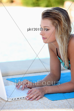Young Woman Using A Laptop By A Swimming Pool Stock Photo