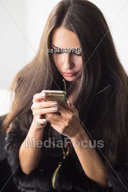 Young Woman Wearing Fur Coat Posing With A Phone Stock Photo