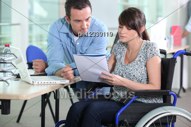 Young Woman In Wheelchair Working With A Male Colleague Stock Photo