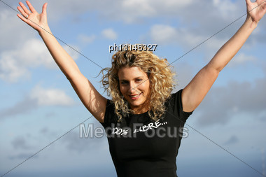 Young Woman With Arms Up Outdoors Stock Photo