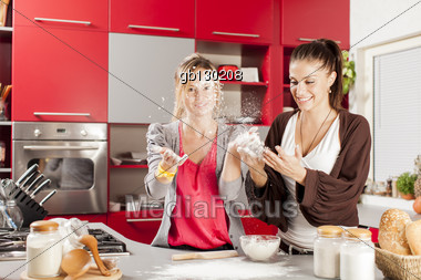 Young women preparing meal in the kitchen Stock Photo