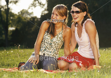 Young Women Sitting in Park Laughing Stock Photo