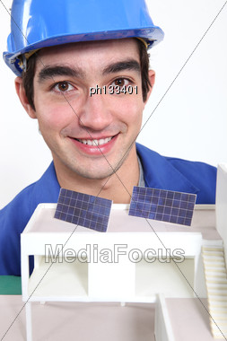 Young Worker With An Architectural Model Showing Solar Panels Stock Photo