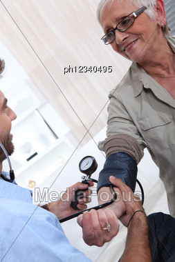 Youngman Taking Old Woman's Blood Pressure Stock Photo
