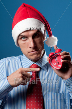 Yuong Man In Red Christmas Hat And Alarm Clock Stock Photo