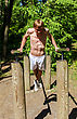 Attractive Man Pull-ups On A Bar In A Forest stock image