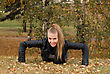 Beauty Female Doing Push Ups In The Park - stock image