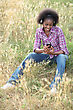 Stock Photo : Casual Stock Photography: Black Woman Seated In High Grass Listening To Favorite Songs