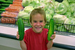Boy at Grocery Store Holding Cucumbers stock photo