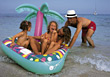 Stock Photo : Kid Stock Photography: Dad pushing his kids on a float at the beach