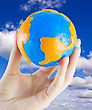 Fluffy Earth W In Hand Against The Blue Sky stock image