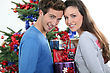 Excited Young Couple Stood By The Christmas Tree stock photography