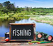 Fishing Tackle And A Blackboard On A Background Of Lake stock photo
