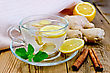 Ginger Tea In A Glass Cup, Lemon, Cinnamon, Ginger, Mint, Napkin Against A Wooden Board stock photo