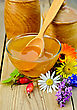 Honey In A Glass Bowl And Wooden Banks, Spoon, Berries Of Briar, Flowers On The Background Of Wooden Boards stock photo
